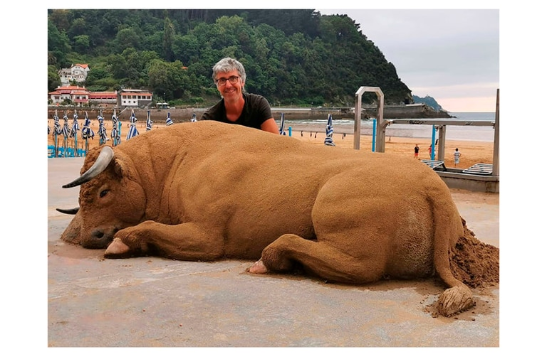 Bastarrika junto a un toro de tamaño real hecho en arena en el malecón de la playa Zarauz