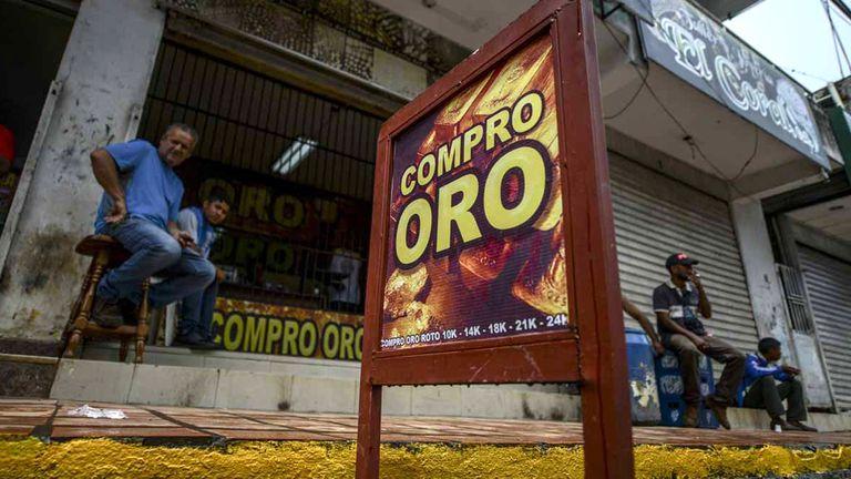 Hombres sentados a las afueras de un negocio de compra de oro en El Callao, estado Bolívar, en el sureste de Venezuela