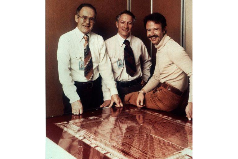 Gordon Moore, Robert Noyce y Andy Grove, de Intel, la empresa que creó el primer cerebro electrónico disponible comercialmente, en 1971. En la foto están con el plano del 8080, un icónico e influyente chip de 1974; es decir, previo a la IBM/PC