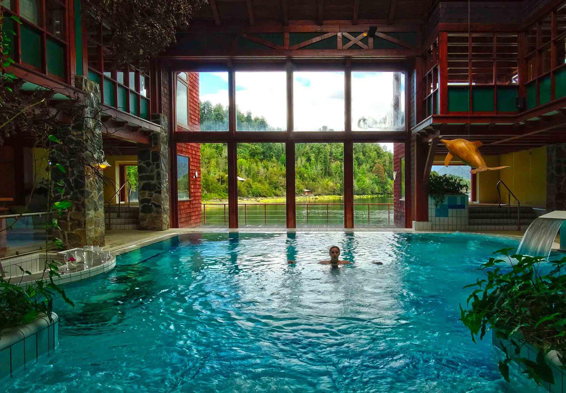 Piscina cubierta con grandes ventanales del Puyuhuapi Lodge.