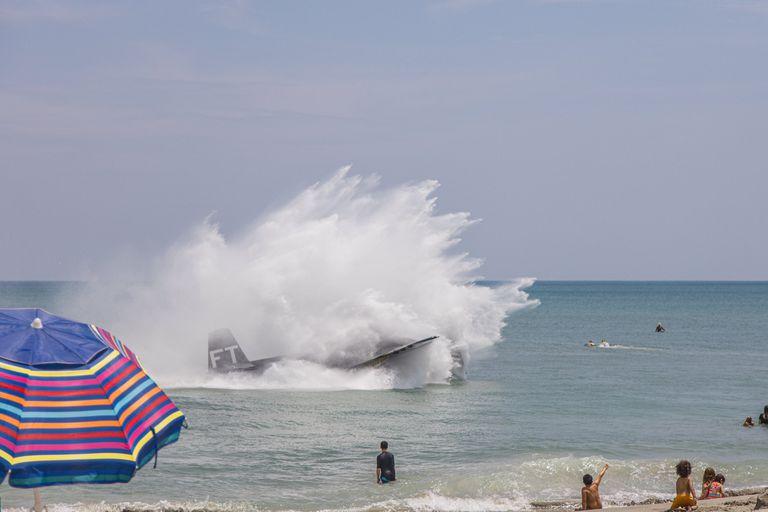 Un antiguo avión de la Segunda Guerra Mundial realizó un aterrizaje de emergencia en las aguas poco profundas de una playa colmada por una multitud de gente