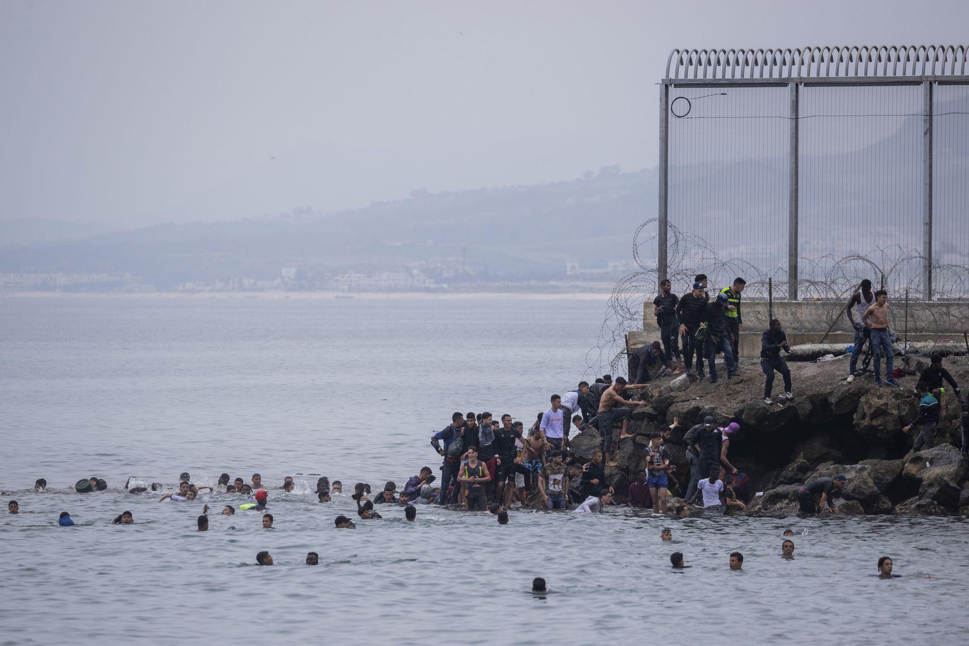 Migrantes cruzan nadando al enclave español de Ceuta, cerca de la frontera de Marruecos y España