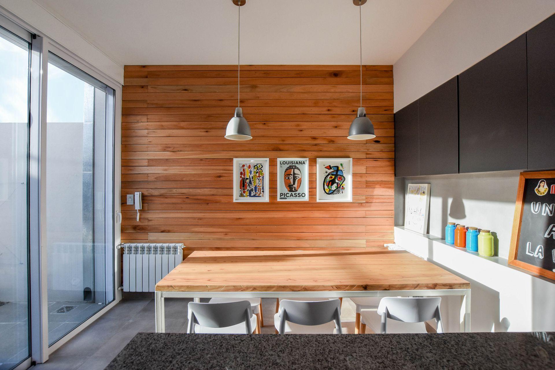 Para compensar del acero, en el comedor revisitó una pared a modo de deck vertical. Mesa con base de hierro pintada de blanco y tapa de paraíso (Estudio MPB) con ruedas, cómoda para llevar al patio. En el mueble de la cabecera, de 15cm de profundidad, guarda frascos y alimentos.