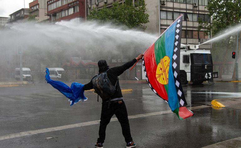 Un hombre con una bandera mapuche se enfrenta a la policía durante una protesta en Santiago de Chile