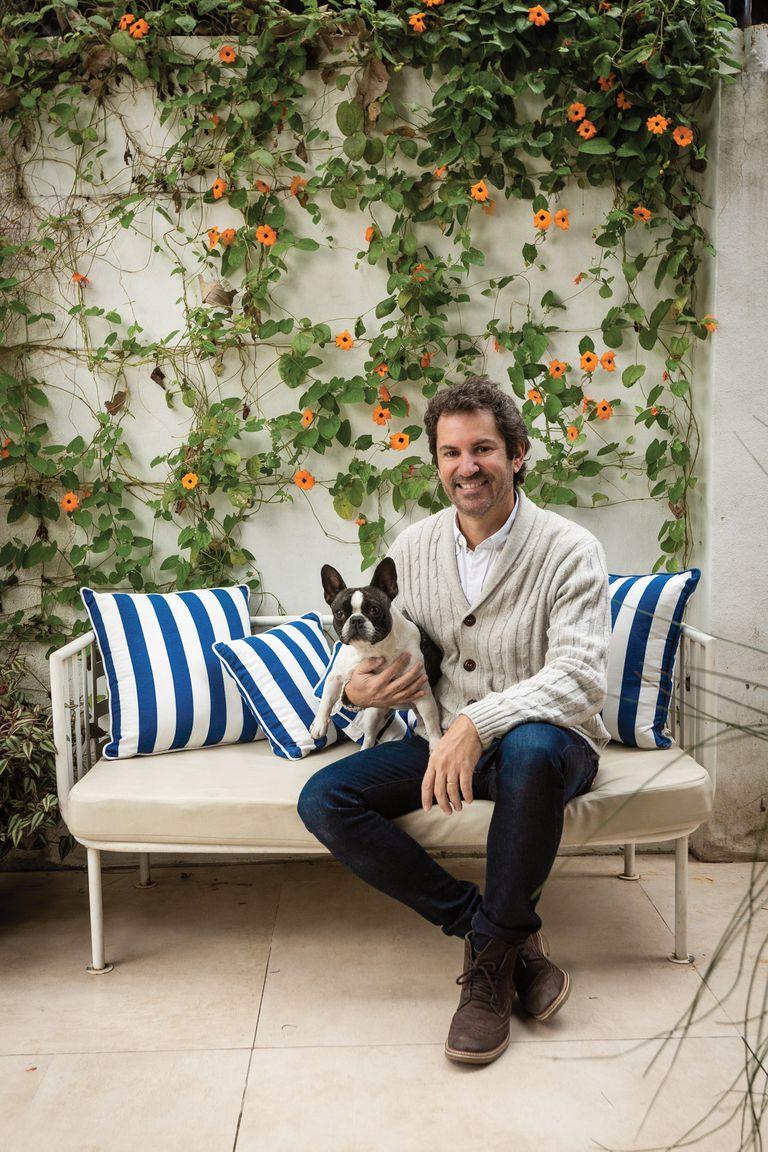 El dueño de casa posa con Pebeta, su bulldog francesa. Detrás de ellos, el jardín vertical que hizo el propio Sebastián.