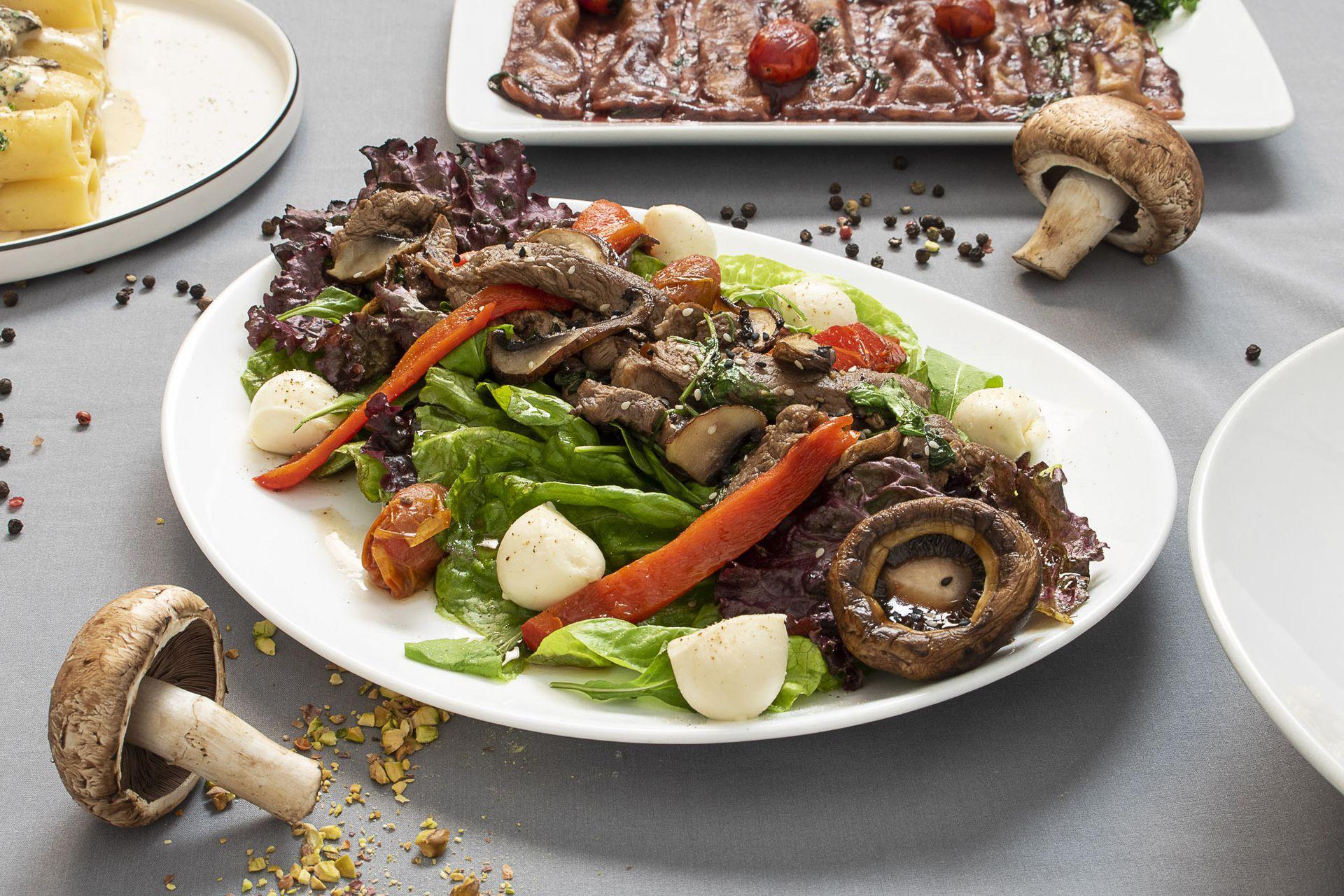 Ensalada tibia de lomo con mix de hojas, portobello y boconcino