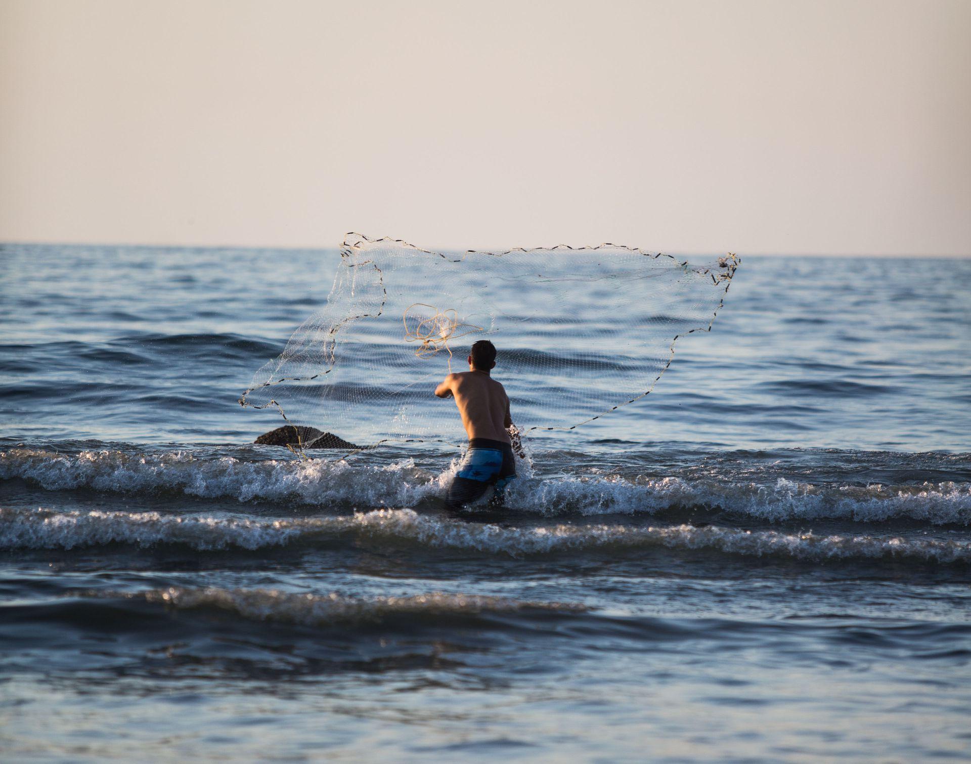 Un pescador artesanal lanza una red en el mar de Sayulita.