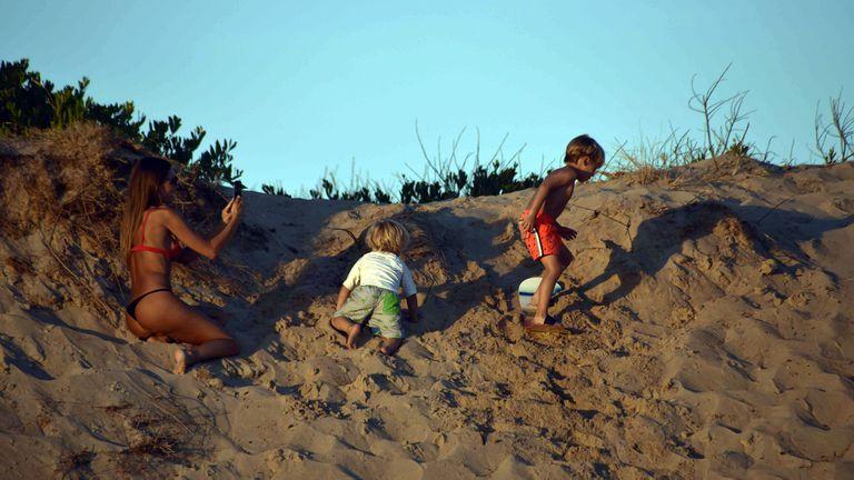 Pampita le saca fotos a sus pequeños que disfrutan de deslizarse en las dunas