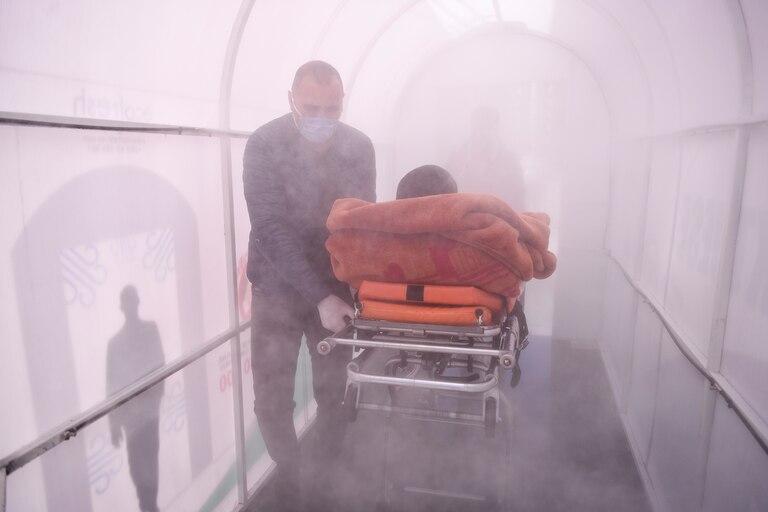 Un trabajador de salud lleva a un paciente a través de una cámara de desinfección configurada como medida preventiva en medio de las preocupaciones sobre la propagación de la Covid-19 frente a un hospital en Mitrovica el 7 de abril de 2020