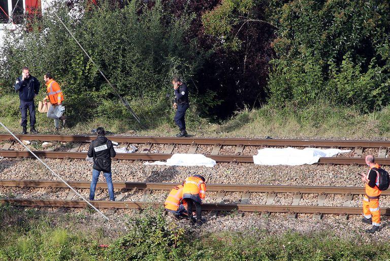 Policías investigan una zona donde un tren atropelló a cuatro personas, dejando tres muertos, en Ciboure, sureste de Francia, el 12 de octubre de 2021. Se cree que las víctimas eran migrantes que descansaban en las vías. (AP Foto/Bob Edme)