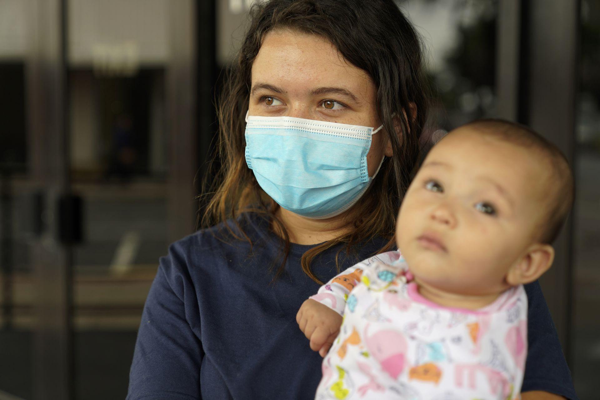 Laura Scalzo, de 20 años, de Honduras, sostiene a su bebé mientras habla en un refugio para migrantes en McAllen, Texas. Scalzo se unió a cientos de personas que viajaban hacia el norte con su bebé de 6 meses y se entregó a los agentes de inmigración que patrullaban una vasta área del sur de Texas