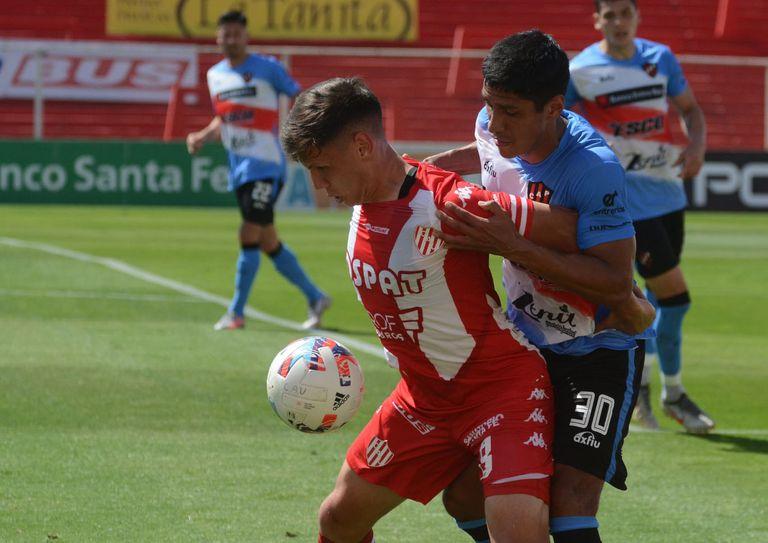 Enzo Roldán, de Unión, cuida la pelota ante la marca de Lucas Kruspzky