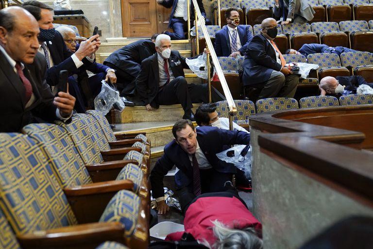 ARCHIVO - En esta foto de archivo del 6 de enero de 2021, gente se refugia cuando los insurrectos tratan de irrumpir en el recinto de la Cámara de Representantes