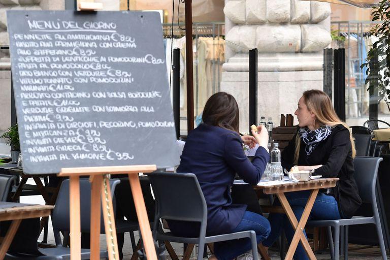 Personas se reúnen a almorzar en la calle Dante el 26 de abril de 2021 en el centro de Milán