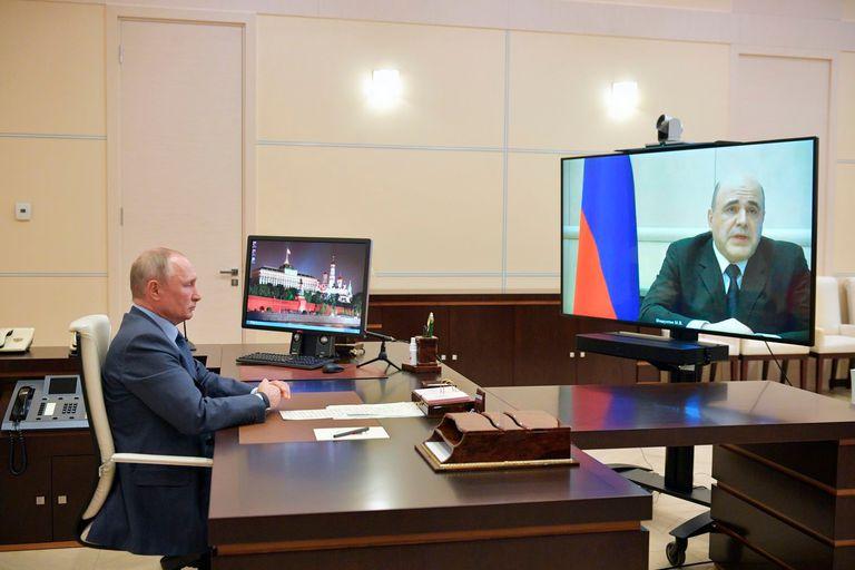 El primer ministros, Mijaíl Mishustin, (en la pantalla) junto a Vladímir Putin por videoconferencia.