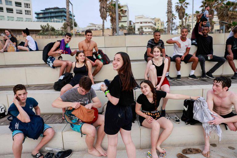 Jóvenes, ya sin barbijo al aire libre, en la ciudad balnearia de Tel Aviv