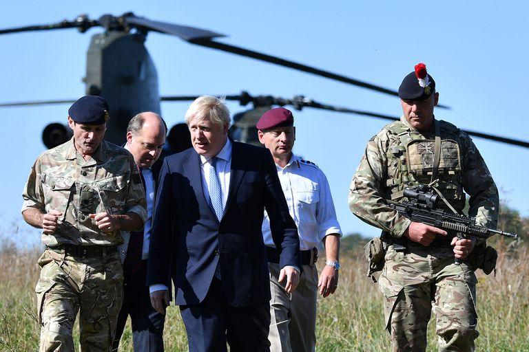 En esta foto del 19 de septiembre de 2019, el primer ministro británico, Boris Johnson llega con el secretario de Defensa británico Ben Wallace para visitar al personal militar en el área de entrenamiento de la llanura de Salisbury, en el suroeste de Inglaterra