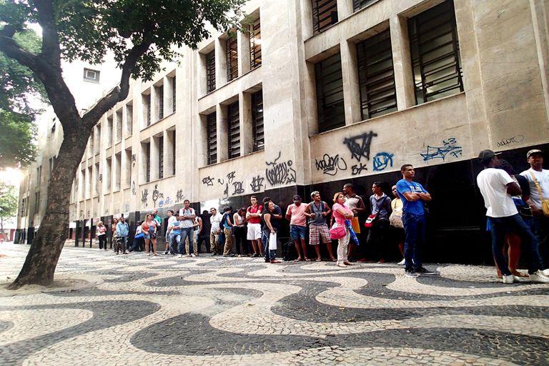 Entre vendedores de mate y bizcochos, la gente que hace fila para cobrar el seguro de desempleo en la sede regional del Ministerio de Trabajo en Río de Janeiro comparte sus dramas