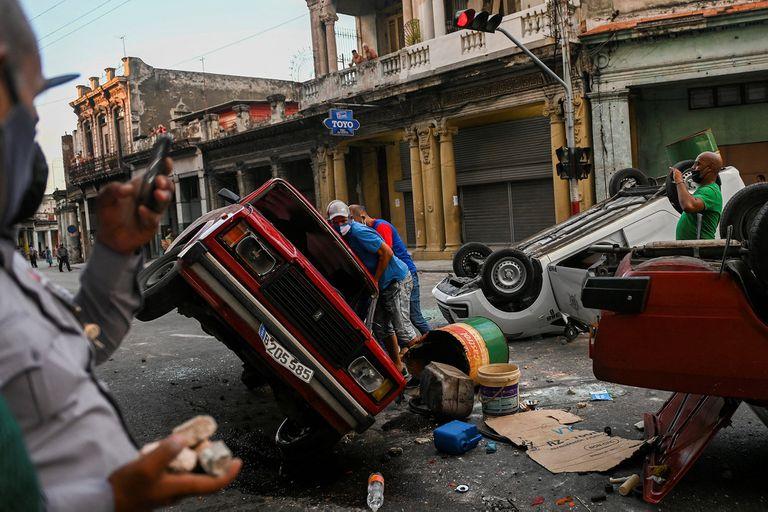 Coches de la policía volcados en la calle durante una manifestación contra el presidente cubano, Miguel Díaz-Canel, en La Habana, en julio pasado