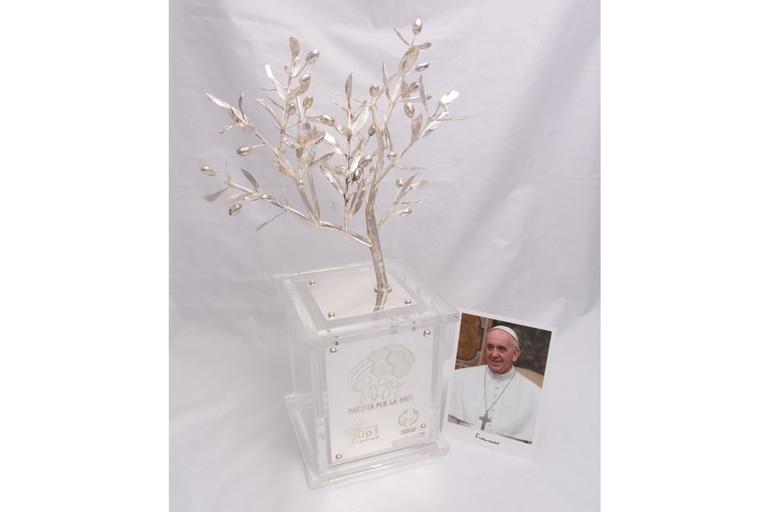El trofeo es un olivo con 24 frutos, 24 olivas que representan a los 12 apóstoles y a los 12 ancianos, es decir, el Antiguo y el Nuevo Testamento