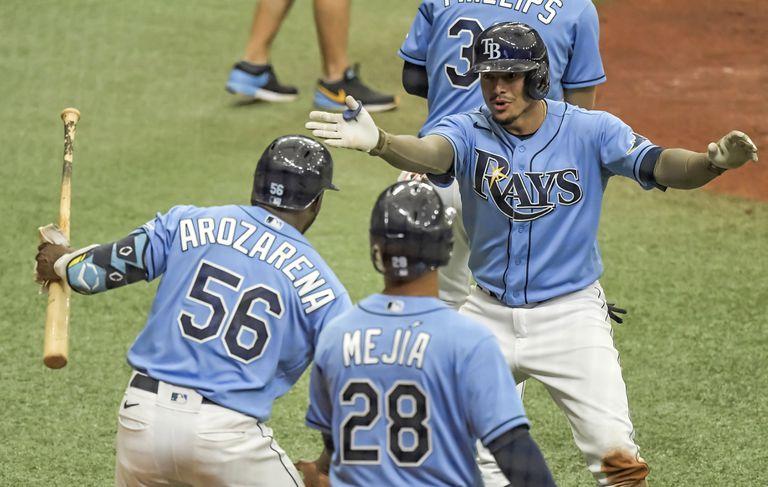 El cubano Randy Arozarena (56) y el dominicano Francisco Mejía (28) felicitan a Willy Adames luego que éste pegó un jonrón de dos carreras para la causa de los Rays de Tampa Bay, en el duelo ante los Mets de Nueva York, el domingo 16 de mayo de 2021, en St. Petersburg, Florida. (AP Foto/Steve Nesius)