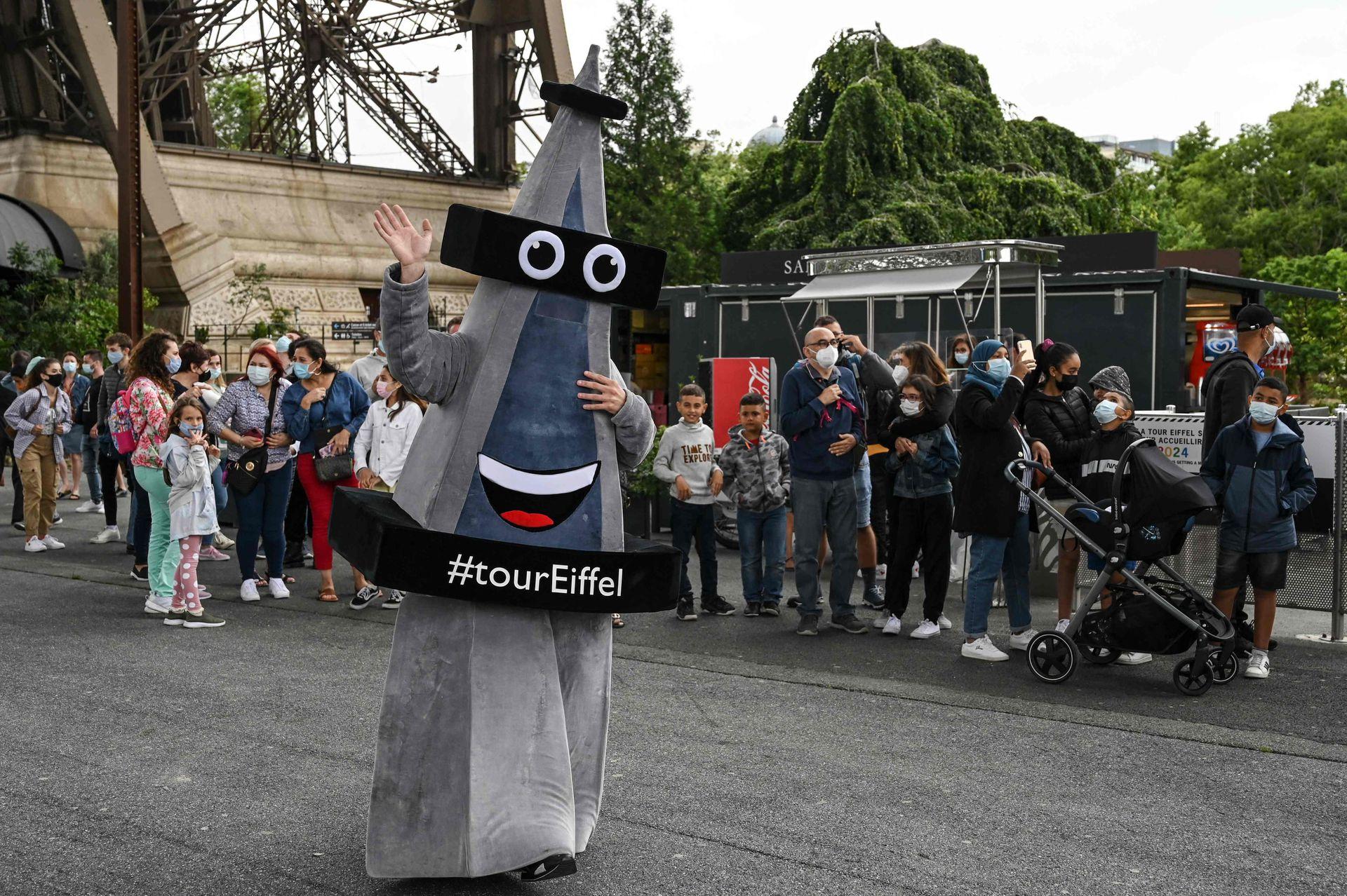 La mascota de la Torre Eiffel saluda mientras los visitantes esperan en la fila antes de visitar la Torre Eiffel en París