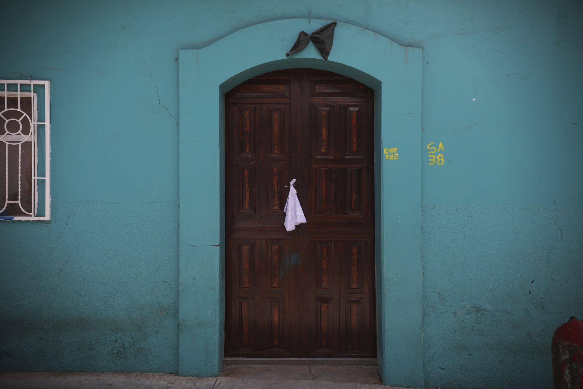 Un pañuelo blanco está atado a la manija de la puerta y un banderín negro en el marco de la puerta de una casa en la ciudad de Pantelho