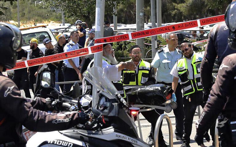 Los rescatistas israelíes retiran un cuerpo de la escena de un ataque en Jerusalén, el lunes 24 de mayo de 2021. Un soldado israelí y un civil fueron apuñalados el lunes cerca de una estación de tren ligero en el este de Jerusalén