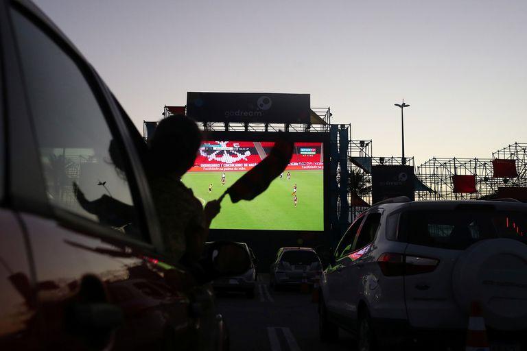 Los fanáticos del fútbol de Flamengo ven el partido del Campeonato Brasileiro entre Flamengo y Atlético Mineiro desde autos durante un autocine, en Río de Janeiro