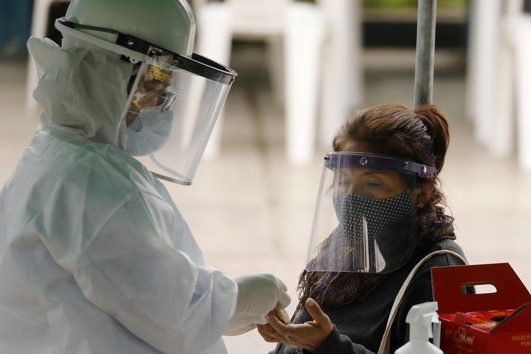 """(200821) -- LIMA, 21 agosto, 2020 (Xinhua) -- Un trabajador de la salud realiza una prueba rápida de la enfermedad causada por el nuevo coronavirus (COVID-19) a una mujer durante el estado de emergencia sanitaria en la municipalidad de Villa María del Triunfo, en Lima, Perú, el 21 de agosto de 2020. Cines, teatros, gimnasios y hasta casinos empiezan a tomar su ritmo en una """"nueva normalidad"""" por la COVID-19 en América Latina, mientras algunos países participan en la fase 3 para probar una vacuna que ayude a combatir el virus. (Xinhua/Mariana Bazo) (mb) (mm) (vf) (dp)"""
