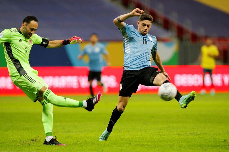 David Ospina, el arquero récord, rechaza la pelota frente a la embestida de Federico Valverde (Photo by SILVIO AVILA / AFP)