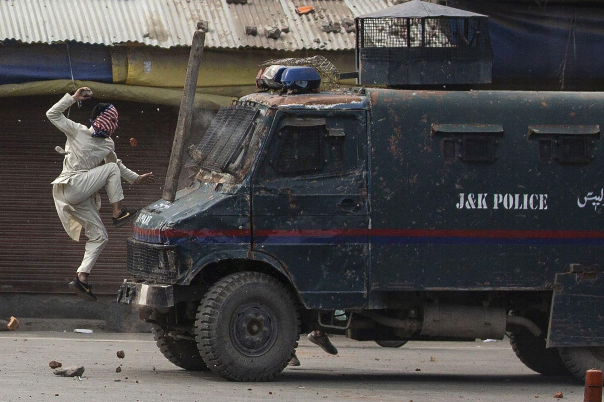 Un manifestante enmascarado de Cachemira salta al capó de un vehículo blindado de la policía de la india mientras le arroja piedras durante una protesta en Srinagar, Cachemira