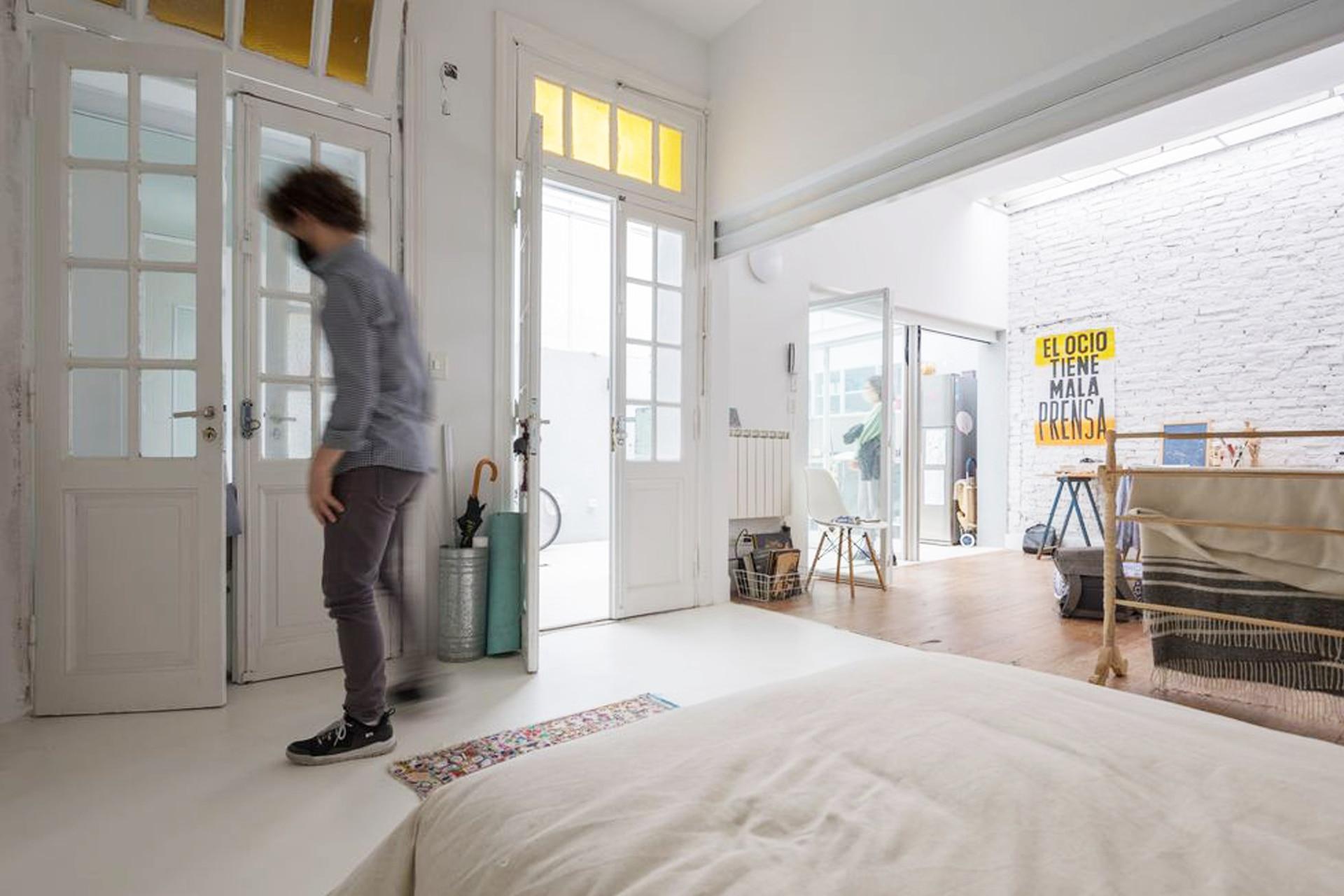 Una doble puerta de vidrio repartido da paso al espacio que precede al baño y funciona como práctico lavadero. Allí están el lavarropas y un mueble para la blanquería.