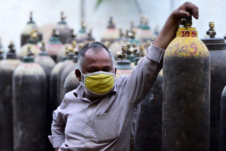Un hombre aguarda para rellenar un tubo de oxígeno en una estación de carga en Allahabad, India el 20 de abril de 2021