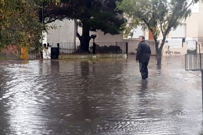 Un hombre cruza la calle inundada