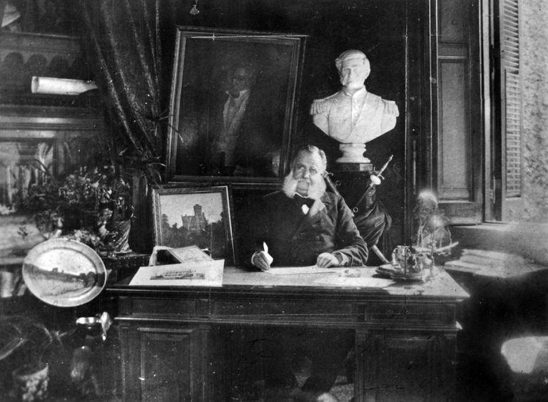 Pastor Obligado retratado en su escritorio, a su lado una pintura de su residencia sobre Avenida Alvear, circa 1886.