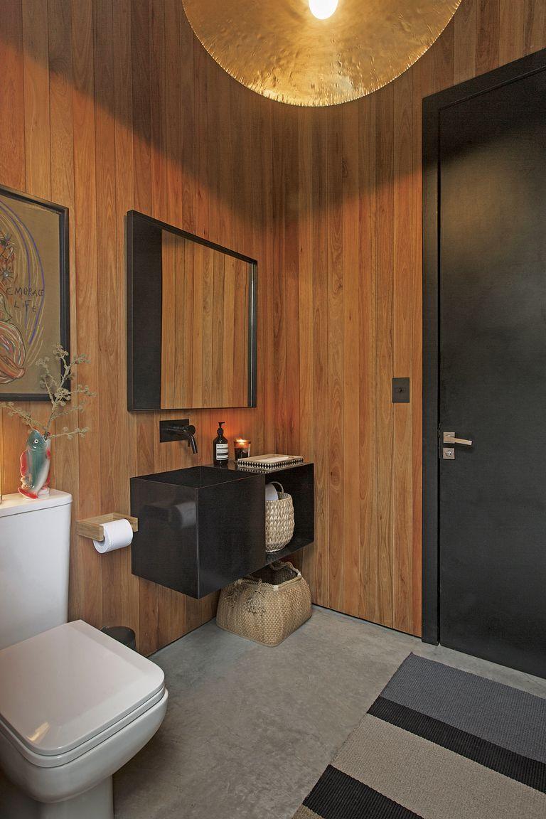 El toilette, también revestido en madera, con bacha de Hermanas Cardonti Home, lámpara techo de Mónica Melhem y alfombra Rugit.
