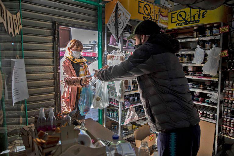Los locales comerciales trabajan con las cortinas metálicas a medio abrir