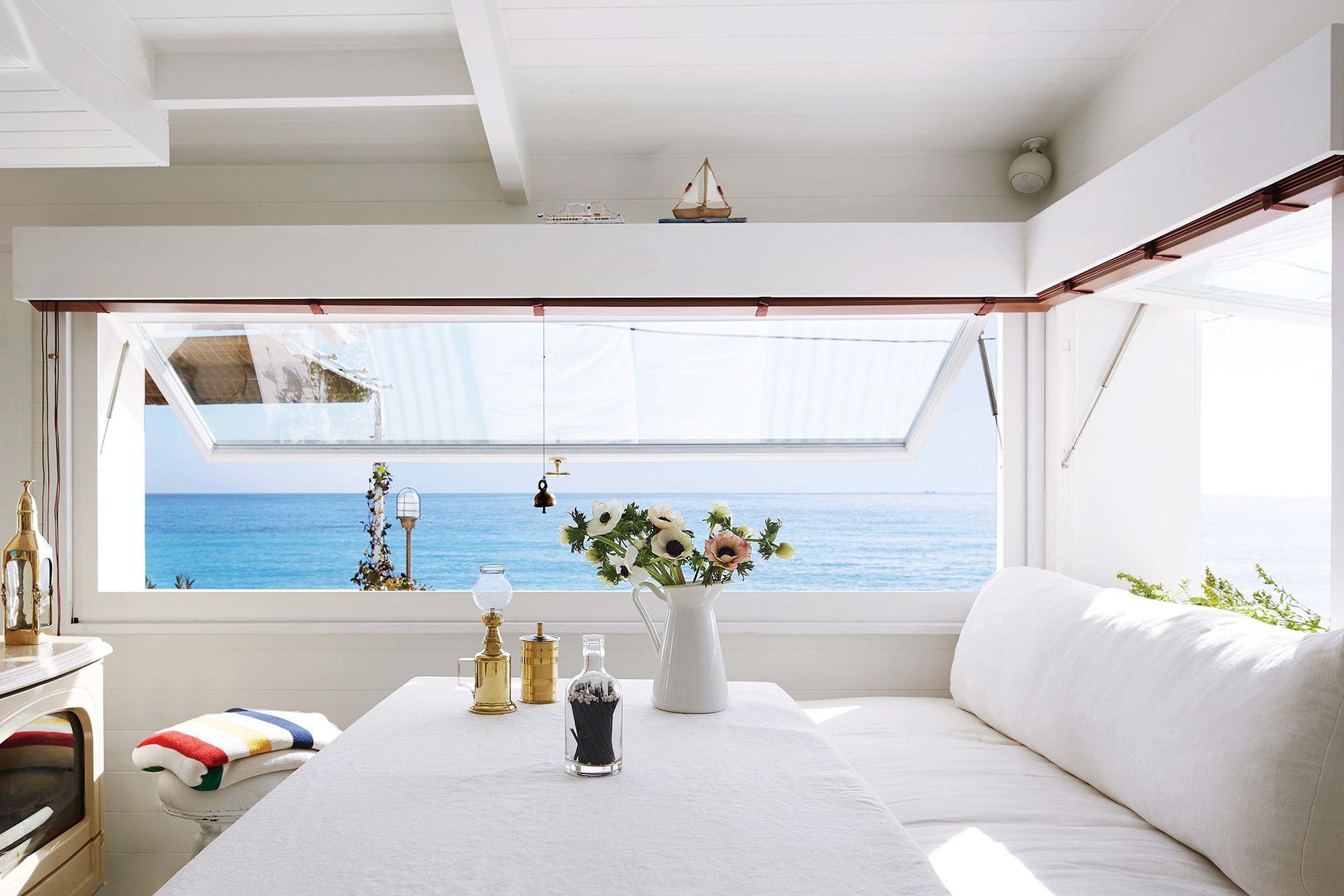 Perpendiculares, dos ventanas batientes con apertura telescópica toman el rincón con vista. Para asimilarlas al clima de hogar, cenefas que ocultan las persianas de madera.