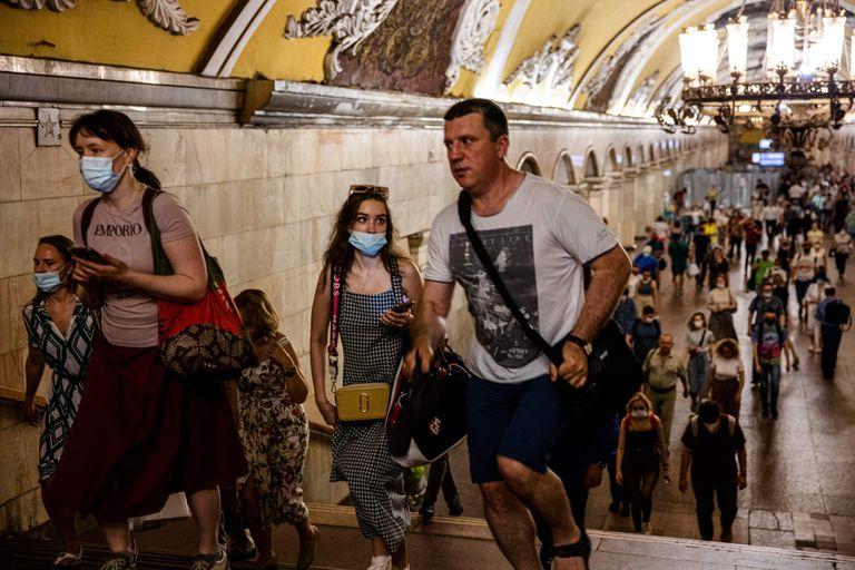 Las personas, algunos con mascarillas, caminan en una plataforma en el metro de Moscú