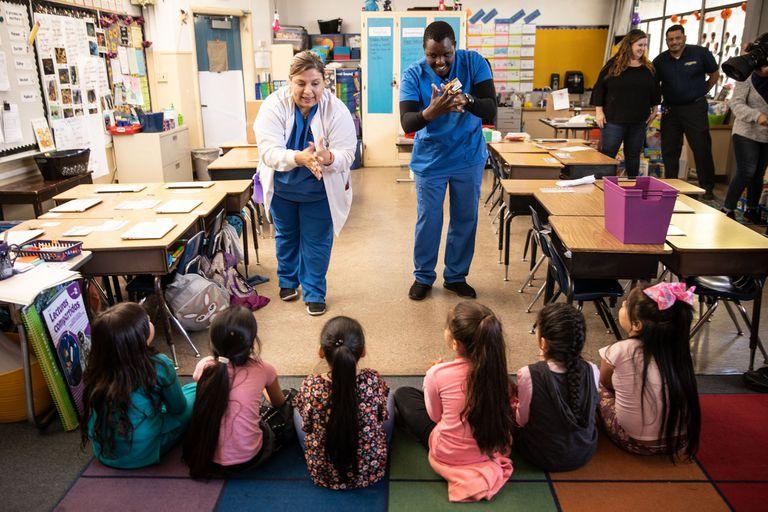 Los estudiantes de enfermería Soledad Lupian, a la izquierda, y Edwin Gituma muestran a los alumnos de primer grado de la Escuela Primaria Ethel Phillips en Sacramento cómo lavarse las manos adecuadamente para reducir la propagación del coronavirus en marzo, antes de que cerraran las escuelas.