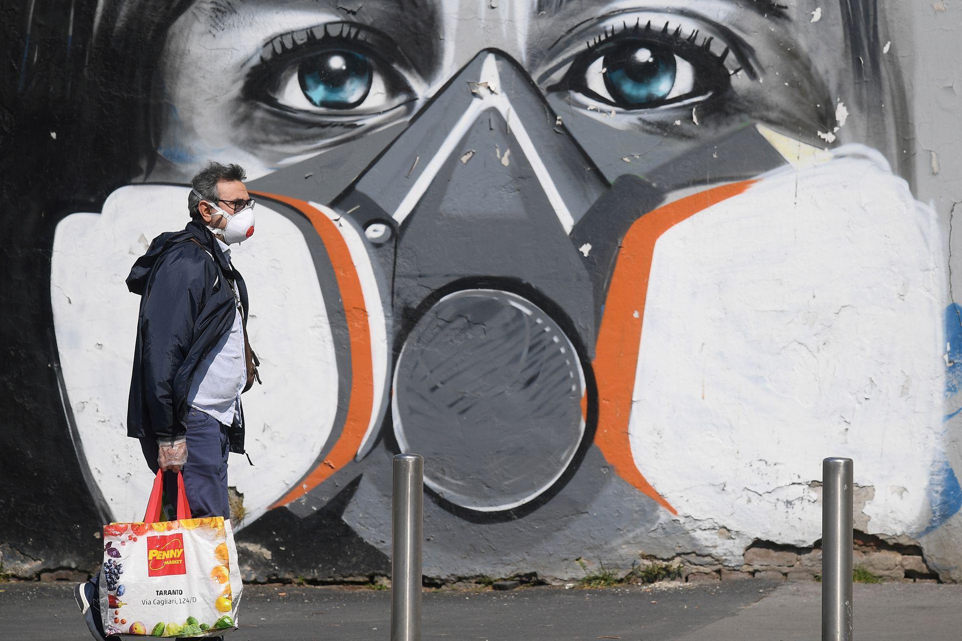 Un hombre camina junto a un mural pintado en Milán