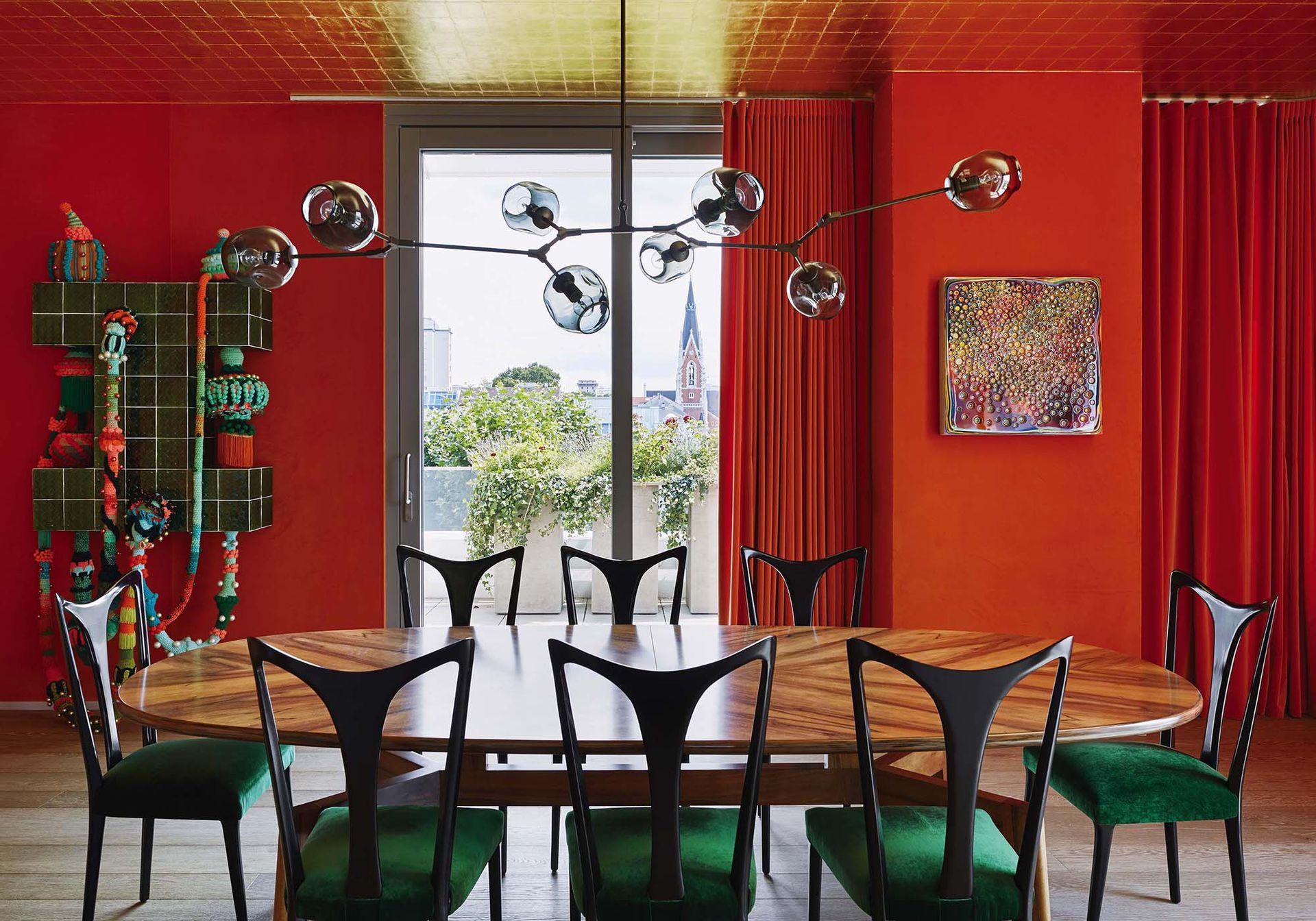 Mesa de nogal (Kerylos Intérieurs), sillas de Guglielmo Ulrich tapizadas con terciopelo y lámpara de la gran Lindsey Adelman. Las cortinas se hicieron con género de Hermès en su naranja característico.