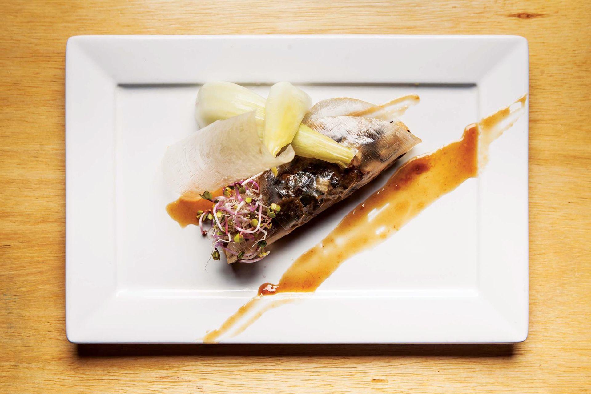 Raviol de papel de arroz relleno de verduras cocidas y hongos con pickle de pencas y reducción de cítricos.