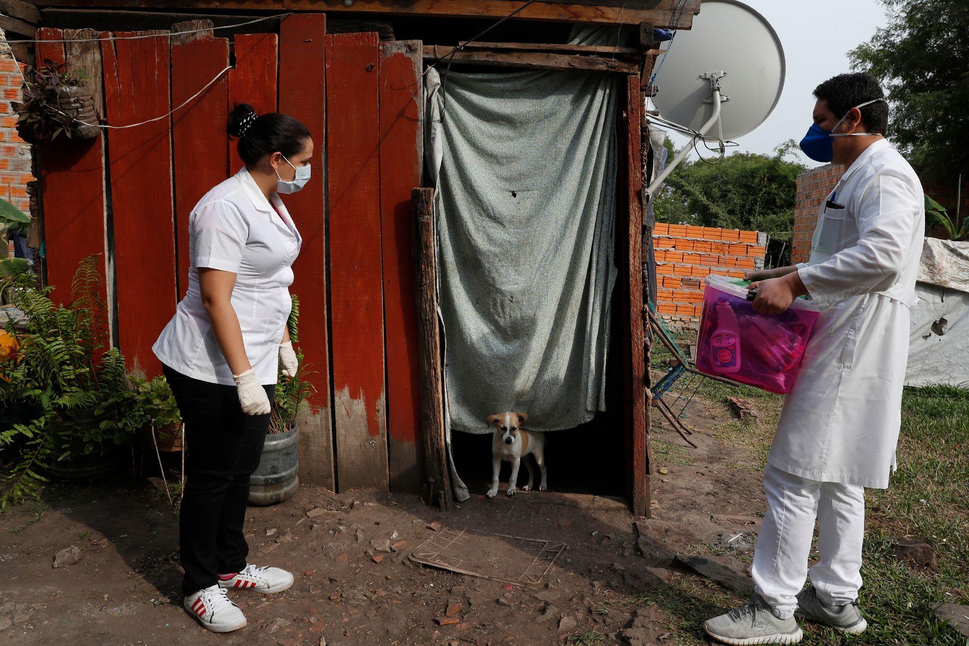 Dos trabajadores del Ministerio de Salud esperan a que el ocupante salga para hacerse la prueba del COVID-19 en Limpio, Paraguay, finalmente la enfemera entró con equipo de protección, por que la mujer que estaba adentro estaba muy enferma