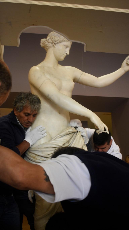 Guantes blancos y sumo cuidado para mover a la escultura que pesa 750 kilogramos.