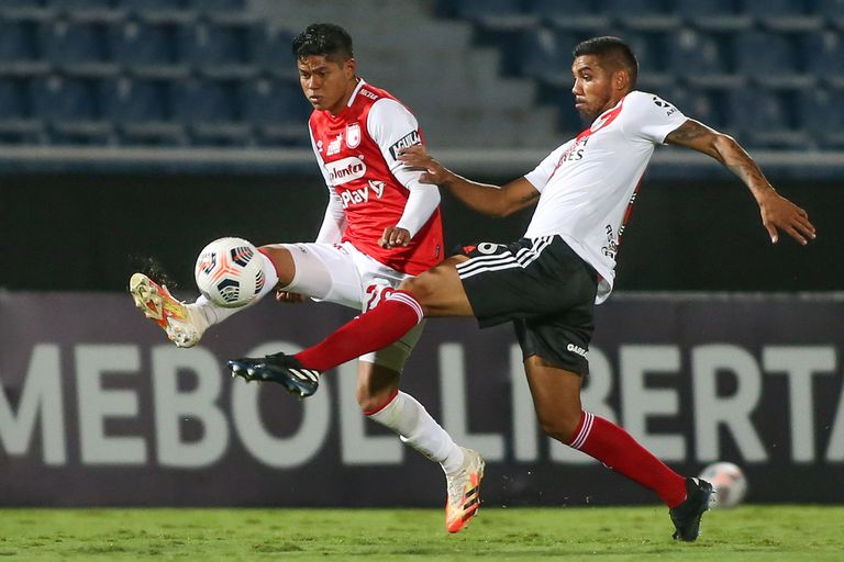 Héctor David Martínez se raspa contra un futbolista colombiano durante el encuentro entre River e Independiente Santa Fe, por la Copa Libertadores.