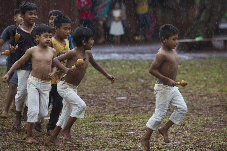 Chicos integrantes del Coro del Fortín Mbororé cantan bajo la lluvia.