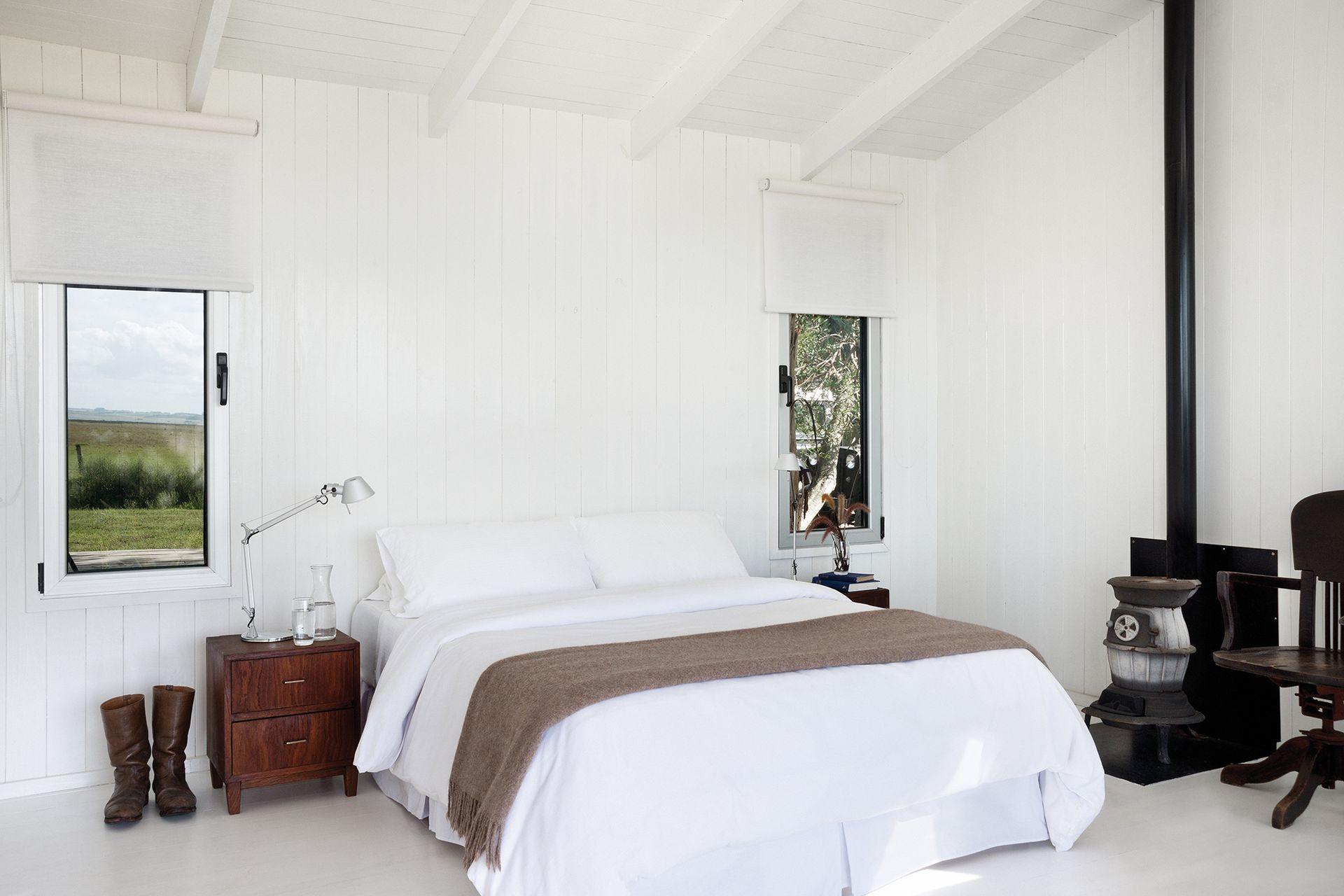 En el cuarto de la cabaña basta con las visuales del campo y la laguna, y la cama cómoda al abrigo de una salamandra de hierro.
