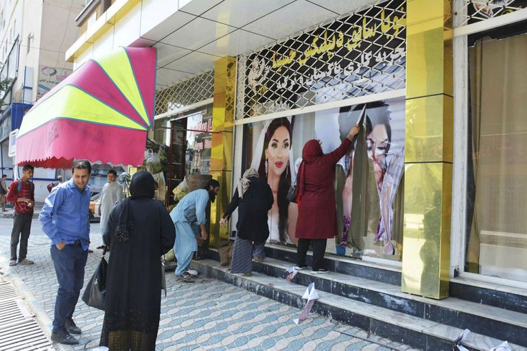 Los trabajadores de un salón de belleza quitan fotografías de mujeres de la pared en Kabul el 15 de agosto de 2021.